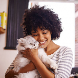 Photograph of woman snuggling a cat
