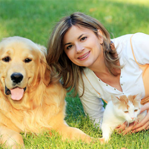 Photograph of woman with dog and cat sitting in grass